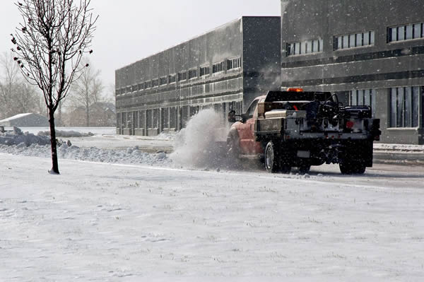 Truck with snow plow removing snow from a public road